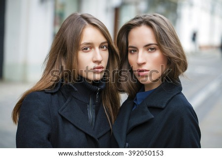 Close Up portrait of two friends in a black coat on the street in the spring - stock photo