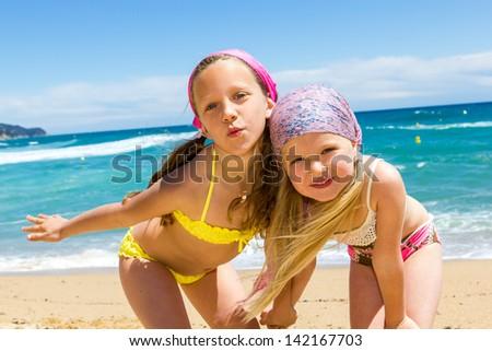 Close up portrait of two girlfriends in swimwear on beach. - stock photo
