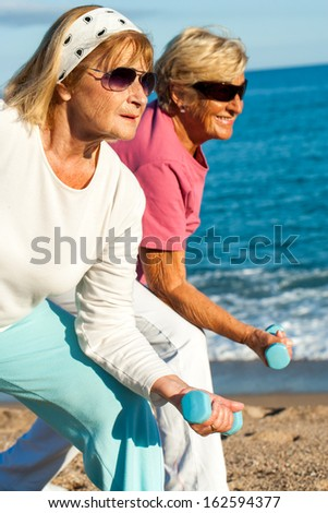 Close up portrait of two golden age women doing early morning workout on beach. - stock photo