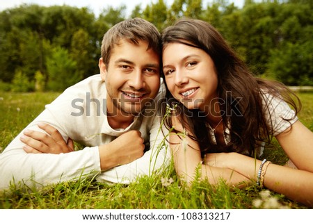 Close-up portrait of two happy lovers resting on the grass - stock photo