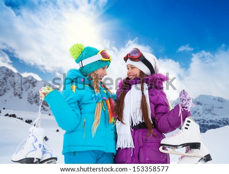 Close-up portrait of two happy smiling Caucasian girls standing outside with ice-skates - stock photo