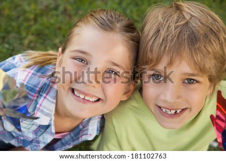 Close-up portrait of two kids holding pinwheelsin the park - stock photo