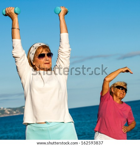 Close up portrait of two senior ladies working out with weights on beach. - stock photo
