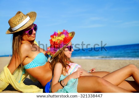 Close up portrait of two suntanned young girls in swimwear sitting together on beach. Women wearing straw hats and fun purple sunglasses looking aside into distance.
