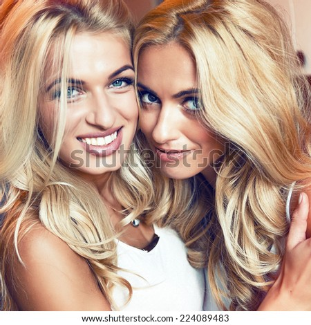 Close up  portrait of two young blonde sisters, hugs a milling laughing and having great time together. Fashion portrait of two best friends. Vintage warm toned colors. - stock photo