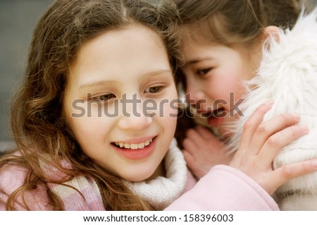Close up portrait of two young girls children sisters in a park during a cold winter day, with one whispering secrets into the others ear, smiling and laughing outdoors. - stock photo