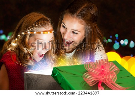 Close up portrait of two young girls opening present with great expectation. - stock photo