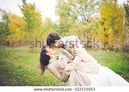 close-up portrait of wedding couples in love hipsters bride in a white dress with flowers and groom in a suit with glasses and bow tie smiling  posing touching embrace on a background of autumn forest - stock photo