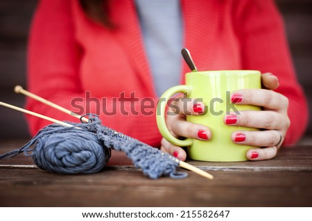 Close up portrait of winter girl knitting and drinking hot drink - stock photo
