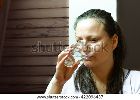 Close up portrait of woman drinking the water on the dark gray background - stock photo