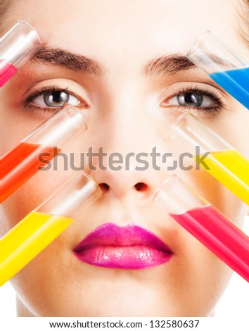 Close-up portrait of woman holding test tubes with makeup liquid of different colors close to her face with eyes open - stock photo