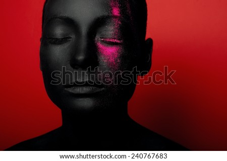 close-up portrait of woman in black paint with magenta dust isolated on red - stock photo