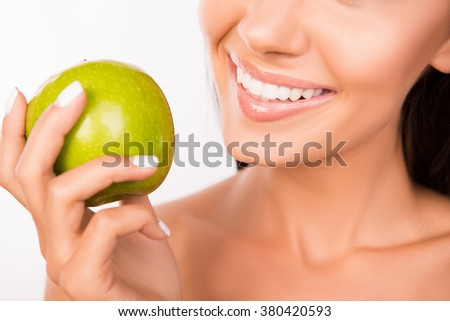 Close up portrait of woman with healthy teeth holding an apple - stock photo