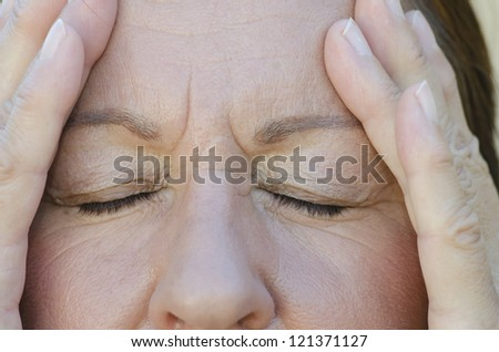 Close Up portrait of worried woman with closed eyes and hands on forehead. - stock photo