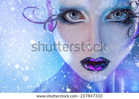 Close up portrait of young adult fashion model looking at camera with creative make up and snow on background in studio - stock photo