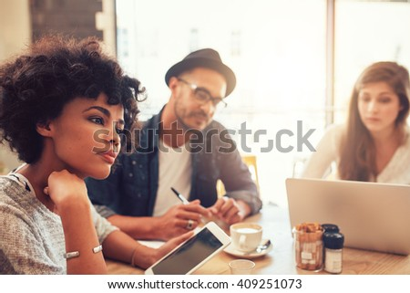 Close up portrait of young african woman with digital tablet and people in background at a cafe table. Young people sitting at a restaurant with laptop and digital tablet. - stock photo