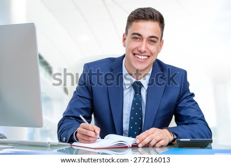 Close up portrait of young attractive businessman in blue suit at desk in office. Young man writing in agenda with pen. - stock photo