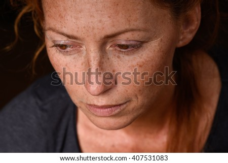 close up portrait of young attractive red hair woman without makeup looking down thinking about problems  - stock photo