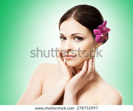 Close-up portrait of young, beautiful and healthy woman with an orchid flower in her hair  - stock photo