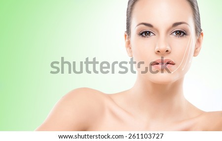 Close-up portrait of young, beautiful and healthy woman with arrows on her face. Green background.  - stock photo