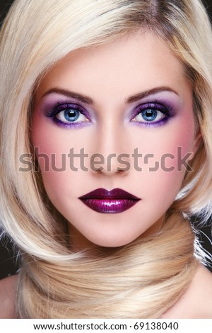 Close-up portrait of young beautiful blond woman with stylish violet make-up - stock photo