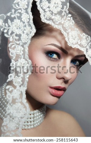 Close-up portrait of young beautiful bride with stylish make-up and bridal veil - stock photo