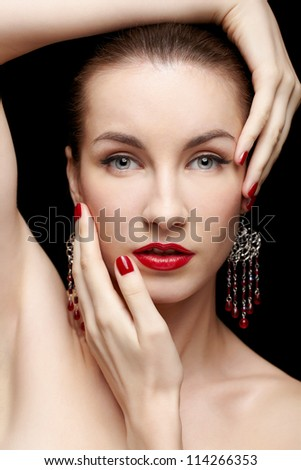 close-up portrait of young beautiful brunette woman in jewelry touching her head with manicured hands - stock photo