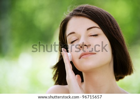Close-up portrait of young beautiful brunette woman putting white cream on her face at summer green park - stock photo