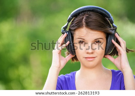 Close-up portrait of young beautiful brunette woman wearing headphones and propping up her face at summer green park. - stock photo
