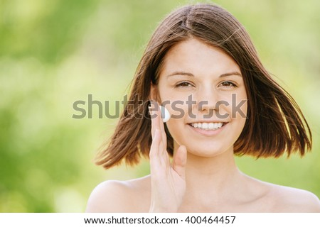 Close-up portrait of young beautiful dark-haired woman putting cream on her face at summer green park. - stock photo