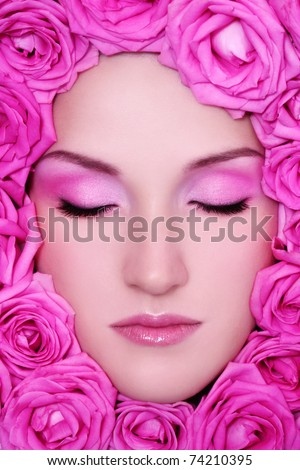Close-up portrait of young beautiful fresh girl with pink make-up and bright roses around her face - stock photo