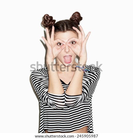Close up portrait of young beautiful girl having fun. Natural makeup and top knot hairdo. White background, not isolated. Inside. - stock photo