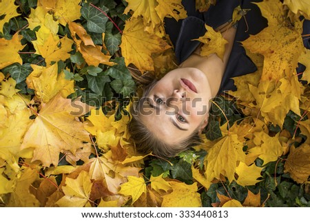 Close-up portrait of young beautiful girl lying on the autumn leaves. - stock photo