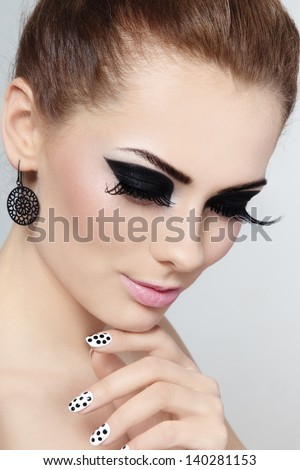 Close-up portrait of young beautiful girl with fancy cat eyes and polka dot manicure - stock photo