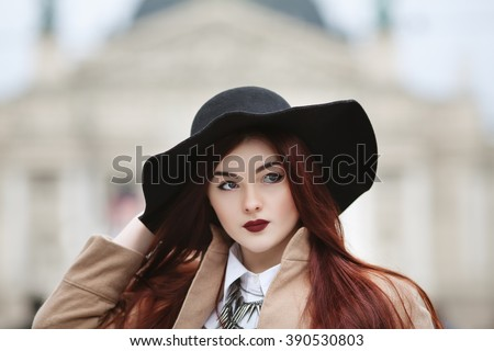 Close up portrait of young beautiful lady wearing stylish classic clothes posing at street of the old city. Girl looking aside. Plus size model. Female fashion concept. Toned - stock photo