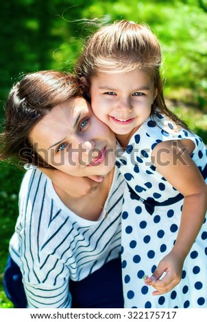 Close up Portrait of Young Beautiful Mother and Daughter. In Sunny Day in Park - stock photo