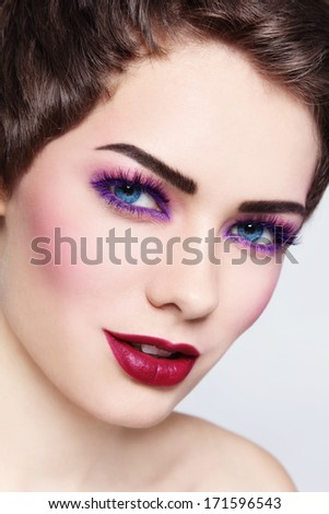 Close-up portrait of young beautiful smiling woman with stylish violet make-up - stock photo