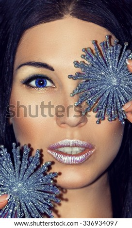 Close-up portrait of young beautiful woman brunette with Christmas decorations ice silver snowflakes. Girl with bright  blue eyes. Fashion make-up in cold silver shades. The Snow Queen. Model shot. - stock photo