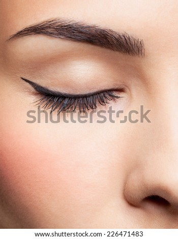 close-up portrait of young beautiful woman's closed eye zone make up with black arrow - stock photo