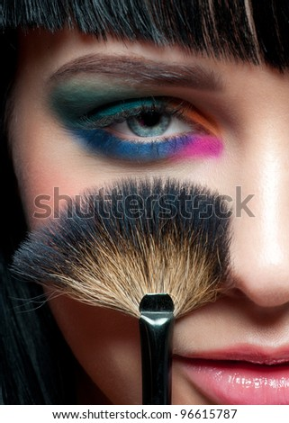 Close-up portrait of young beautiful woman with colorful stylish make-up and with brush for makeup - stock photo