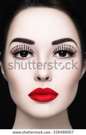 Close-up portrait of young beautiful woman with fancy false eyelashes and matte red lipstick - stock photo