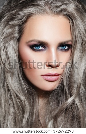 Close-up portrait of young beautiful woman with long grey hair and stylish smoky eyes make-up - stock photo