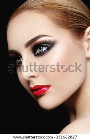 Close-up portrait of young beautiful woman with red lips and smoky eyes - stock photo