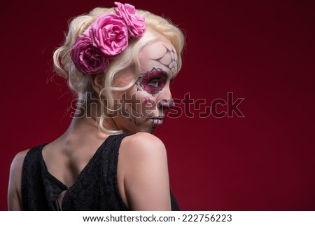 Close-up portrait of young blond girl with sad face with Calaveras makeup and three rose flowers in her hair looking aside with a fright isolated on red background with copy place - stock photo
