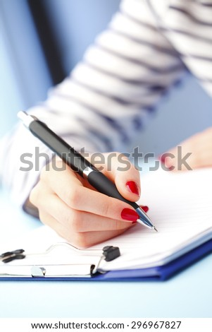 Close-up portrait of young businesswoman sitting at desk and filling IQ test while sitting at desk. - stock photo