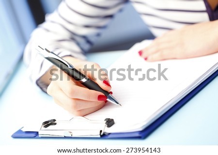 Close-up portrait of young businesswoman sitting at office while fill the application form on job interview.  - stock photo