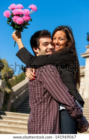 Close up portrait of young couple embracing outdoors with flower bouquet. - stock photo