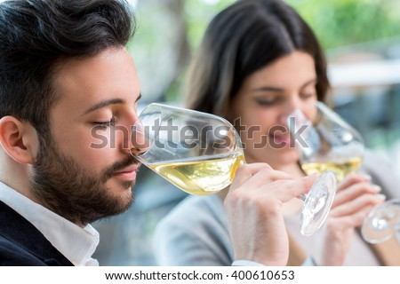 Close up portrait of young couple tasting white wine tasting. - stock photo