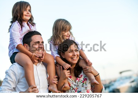 Close up portrait of young couple with kids on shoulders at sunset. - stock photo