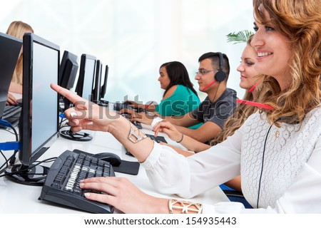 Close up portrait of young female student pointing at blank computer screen in office. - stock photo